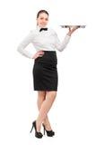 Porträt in voller Länge einer Kellnerin mit dem Querbinder, der ein leeres anhält Lizenzfreies Stockbild
