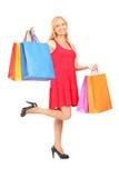 Porträt in voller Länge einer reifen Frau, die mit Einkaufstaschen aufwirft Stockfoto