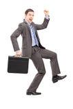 Porträt in voller Länge eines aufgeregten Geschäftsmannes mit einem Aktenkoffer Stockfotos
