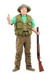 Porträt in voller Länge eines Jägers, der ein Gewehr anhält und ein Th gibt Lizenzfreie Stockbilder