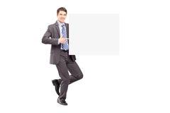 Porträt in voller Länge eines jungen Geschäftsmannes, der eine Platte hält Stockfotos