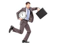 Porträt in voller Länge eines jungen Geschäftsmannes, der spät läuft Stockbild