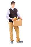 Porträt in voller Länge eines jungen Mannes, der einen beweglichen Kasten anhält Stockfotografie