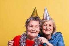 Porträt von ältere Frauen im Studio auf einem gelben Hintergrund Champagne mit den Fliegenballonen und Sankt-Hut lokalisiert Stockfotos