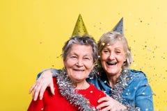 Porträt von ältere Frauen im Studio auf einem gelben Hintergrund Champagne mit den Fliegenballonen und Sankt-Hut lokalisiert Stockbild
