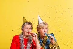 Porträt von ältere Frauen im Studio auf einem gelben Hintergrund Champagne mit den Fliegenballonen und Sankt-Hut lokalisiert Stockfotografie