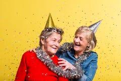 Porträt von ältere Frauen im Studio auf einem gelben Hintergrund Champagne mit den Fliegenballonen und Sankt-Hut lokalisiert Lizenzfreies Stockbild