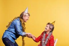 Porträt von ältere Frauen im Studio auf einem gelben Hintergrund Champagne mit den Fliegenballonen und Sankt-Hut lokalisiert Lizenzfreie Stockfotos