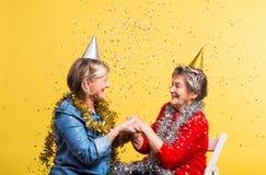 Porträt von ältere Frauen im Studio auf einem gelben Hintergrund Champagne mit den Fliegenballonen und Sankt-Hut lokalisiert Lizenzfreie Stockbilder