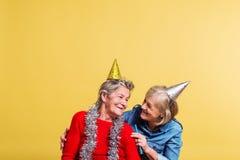 Porträt von ältere Frauen im Studio auf einem gelben Hintergrund Champagne mit den Fliegenballonen und Sankt-Hut lokalisiert Lizenzfreies Stockfoto