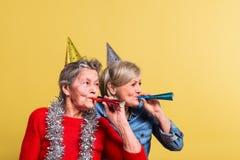 Porträt von ältere Frauen im Studio auf einem gelben Hintergrund Champagne mit den Fliegenballonen und Sankt-Hut lokalisiert Lizenzfreie Stockfotografie