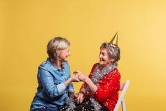 Porträt von ältere Frauen im Studio auf einem gelben Hintergrund Champagne mit den Fliegenballonen und Sankt-Hut lokalisiert Stockbilder