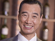 Porträt von älteren lächelnden bereitstehenden Weinflaschen des Geschäftsmannes, Nahaufnahme Stockfotos