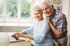 Porträt von älteren Paaren unter Verwendung des Laptops Stockbild