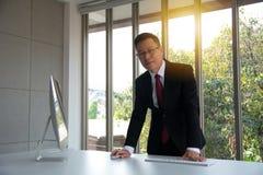 Porträt von überzeugtem in formal gekleideter reifer Geschäftsmannstellung stockbild