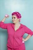 Porträt von anhebenden Gewichten der jungen Frau über farbigem Hintergrund Lizenzfreies Stockfoto