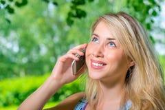 Porträt von attraktiven jungen Blondinen mit dem Telefon stockfotos
