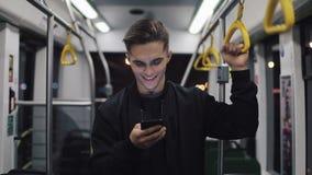 Porträt von attraktiven Männern hält den Handlauf, unter Verwendung des Smartphone, der öffentlich Transport steht Stadt beleucht stock footage
