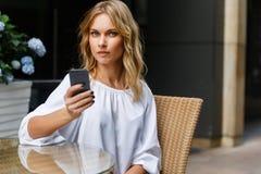 Porträt von Blondinen sitzend im Café mit Smartphone Lizenzfreie Stockfotos