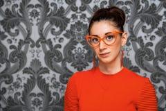 Porträt von Brunette im orange Kleid und in den orange Gläsern auf einem grauen Hintergrund Lizenzfreie Stockfotos