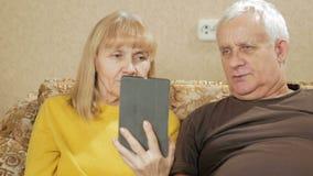 Porträt von den älteren digitale Tablette haltenen und beim Sitzen lächelnden Paaren auf Sofa im Wohnzimmer stock footage