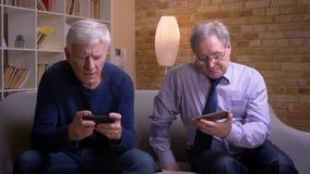Porträt von den älteren männlichen Freunden, die jedes in eigenem Smartphone sitzen und sich aufmerksam und ernsthaft besprechen stock footage