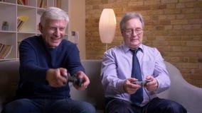 Porträt von den älteren männlichen Freunden, die Videospiel eins von ihnen spielen, verliert und erhält extrem traurig und deprim stock footage