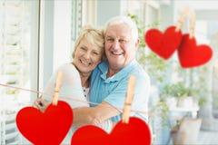 Porträt von den älteren Paaren, die gegen die Herzen hängen an der Linie sich umfassen Lizenzfreies Stockfoto