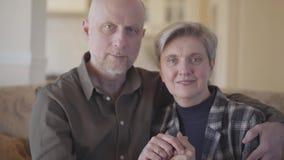 Porträt von den älteren Paaren, die ihnen Fotografie zur Kamera zeigen, als Mann und Frau sehr jung waren S-Klotz, ungeordnet stock video footage