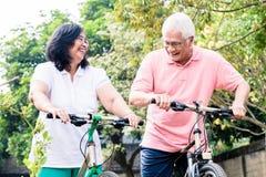 Porträt von den aktiven älteren Paaren, die auf Fahrrädern stehen Stockfoto