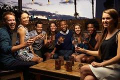Porträt von den Freunden, die heraus Nacht an der Dachspitzen-Bar genießen Lizenzfreie Stockfotos