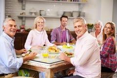 Porträt von den Freunden, die zu Hause Mahlzeit zusammen genießen lizenzfreie stockfotos