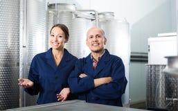 Porträt von den freundlichen zwei Mitarbeitern, die auf Weinfabrik stehen Stockbild