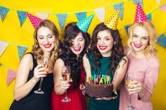Porträt von den frohen Freunden, die Kamera auf Geburtstagsfeier rösten und betrachten Lächelnde Mädchen mit Gläsern Champagner lizenzfreie stockfotografie