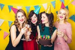 Porträt von den frohen Freunden, die Kamera auf Geburtstagsfeier rösten und betrachten Lächelnde Mädchen mit Gläsern Champagner stockfoto