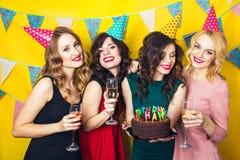 Porträt von den frohen Freunden, die Kamera auf Geburtstagsfeier rösten und betrachten Lächelnde Mädchen mit Gläsern Champagner stockfotos