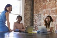 Porträt von den Geschäftsfrauen, die im Sitzungssaal zusammenarbeiten Lizenzfreies Stockfoto