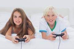 Porträt von den Geschwister, die Videospiele spielen Stockfotografie