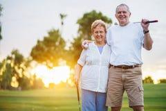 Porträt von den glücklichen älteren Paaren, die das Golf genießt Ruhestand spielen stockbilder