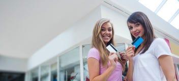 Porträt von den glücklichen Frauen, die ihre Kreditkarten im Mall zeigen Stockbilder