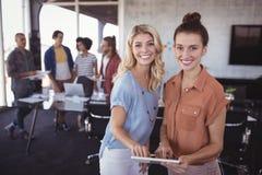 Porträt von den glücklichen Geschäftsfrauen, die digitale Tablette mit kreativem Team halten lizenzfreie stockbilder