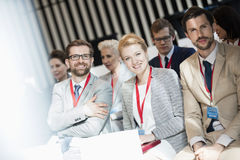 Porträt von den glücklichen Geschäftsleuten, die in der Seminarhalle sitzen Lizenzfreie Stockbilder