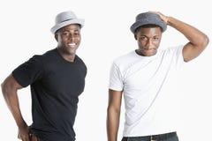 Porträt von den glücklichen jungen Afroamerikanermännern, die Hüte über grauem Hintergrund tragen lizenzfreie stockbilder
