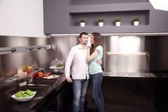 Porträt von den glücklichen jungen Paaren, die zusammen in der Küche kochen Stockbild