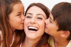 Porträt von den hispanischen Kindern, die Mutter küssen Lizenzfreie Stockfotos