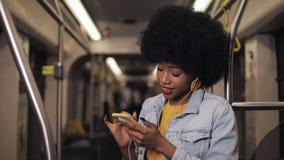 Porträt von den jungen Afroamerikanerfrauen in den Kopfhörern hörend Musik und am Handy öffentlich grasend stock video footage