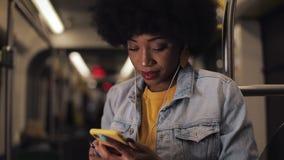Porträt von den jungen Afroamerikanerfrauen in den Kopfhörern hörend Musik und am Handy öffentlich grasend stock footage