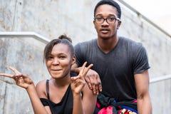 Porträt von den jungen Afroamerikanerpaaren, die lustiges Gesichter whi machen Stockbilder