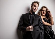 Porträt von den jungen attraktiven Paaren, die am Studio aufwerfen, kleidete in der schwarzen modernen Kleidung an. Lizenzfreies Stockfoto