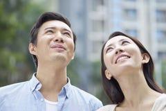 Porträt von den jungen chinesischen Paaren, die oben schauen u. im Freien im Garten lächeln Stockfotos
